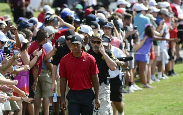 Tiger Woods, foreground, approaches the ninth hole during the final round of the Tour Championship golf tournament Sunday, Sept. 23, 2018, in Atlanta. (AP Photo/John Amis)