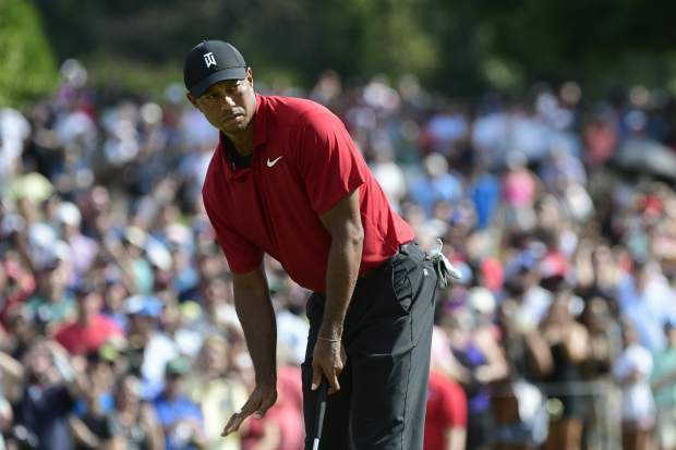 Tiger Woods motions for his putt for birdie to slow down as it passes the ninth hole during the final round of the Tour Championship golf tournament Sunday, Sept. 23, 2018, in Atlanta. (AP Photo/John Amis)