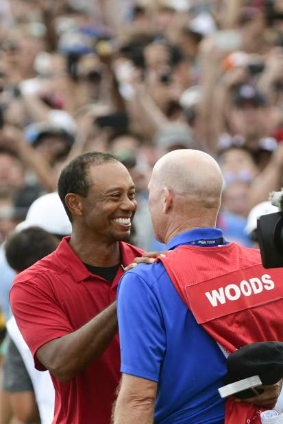 Tiger Woods and caddie Joe LaCava, right, congratulate each other after winning the Tour Championship golf tournament Sunday, Sept. 23, 2018, in Atlanta. (AP Photo/John Amis)