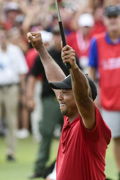 Tiger Woods celebrates after picking up his putt for par on the 18th green to win the final round of the Tour Championship golf tournament Sunday, Sept. 23, 2018, in Atlanta. (AP Photo/John Amis)