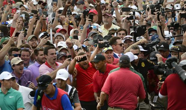 Tiger Woods, lower center, and Rory McIlroy, lower left, emerge from a horde of fans following Tiger on their way to the 18th green during the final round of the Tour Championship golf tournament Sunday, Sept. 23, 2018, in Atlanta. (AP Photo/John Amis)