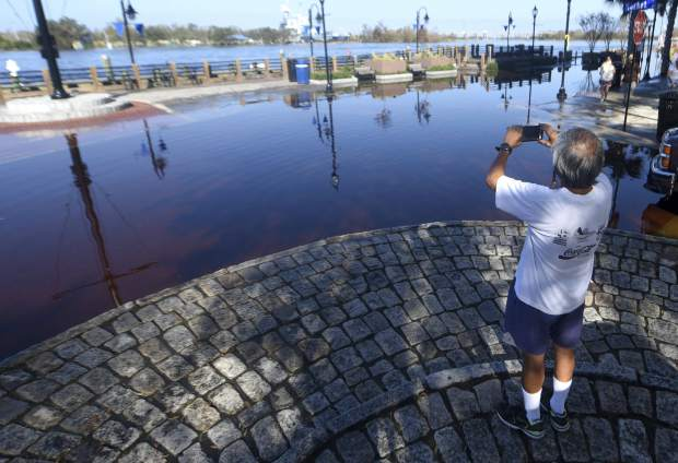 Godfrey Guerzon takes a picture of floodwaters from the Cape Fear River at the foot of Market St in downtown Wilmington, N.C., Sunday, September 23, 2018. The river is expected to crest on Monday night. (Matt Born/The Star-News via AP)