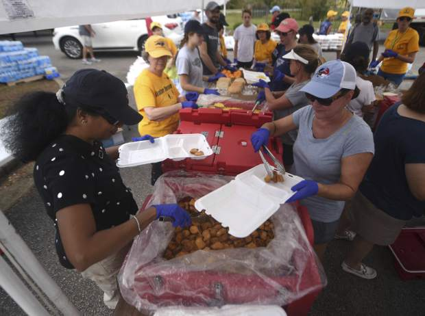 Auxilia Gerard, left, and Lou Anne Liverman help to fill boxes for individual meals at the NC Baptist Men's relief site at First Baptist Activity Center in Wilmington N.C., Sunday, September 23, 2018. The organization was distributing more than 16,000 meals on Sunday. (Matt Born/The Star-News via AP)