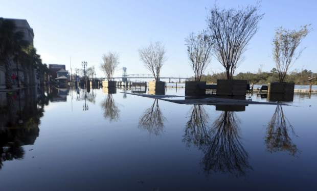Floodwaters from the Cape Fear River cover Water St. in downtown Wilmington, N.C., Sunday, Sept. 23, 2018. (Matt Born/The Star-News via AP)