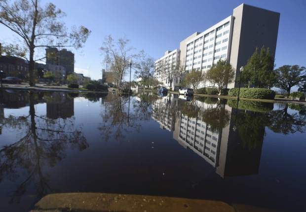 The Hotel Ballast is reflected in floodwaters from the Cape Fear River along Water St. in downtown Wilmington, N.C., Sunday, Sept. 23, 2018. The river is expected to crest on Monday night. (Matt Born/The Star-News via AP)
