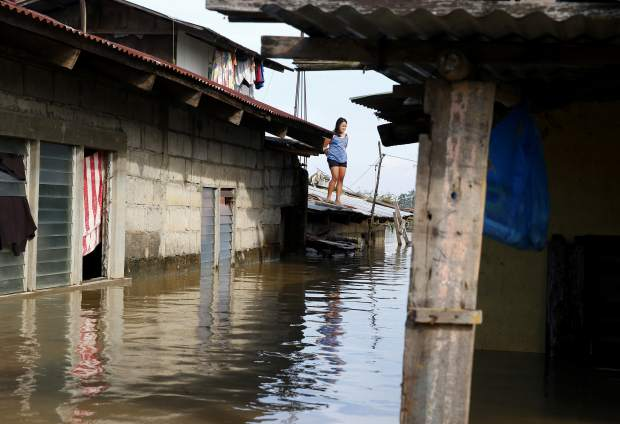 FILE - In this Monday, Sept. 17, 2018 file photo, a resident stands on the roof of her house amidst flooding brought about by Typhoon Mangkhut which barreled into northeastern Philippines during the weekend and inundated low-lying areas in its 900-kilometer wide cloud band, in Calumpit township, Bulacan province north of Manila, Philippines. With global temperatures rising, superstorms taking their deadly toll and a year-end deadline to firm up the Paris climate deal, leaders at this year's U.N. General Assembly are feeling a sense of urgency to keep up the momentum on combating climate change. Monday, Sept. 17, 2018(AP Photo/Bullit Marquez, file)