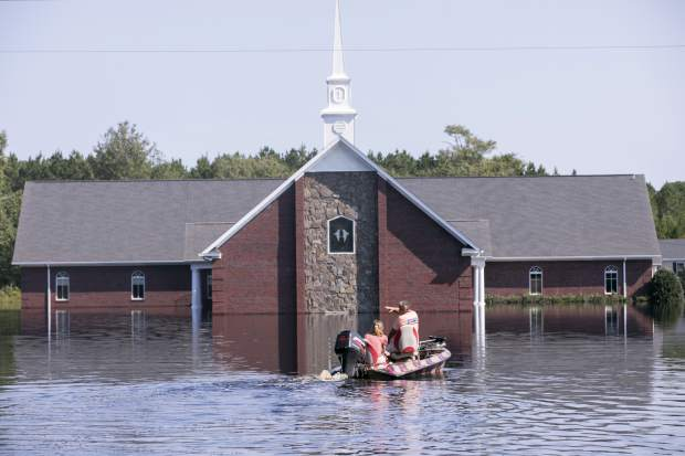 Marvin Singleton and Michele Larrimore motor past the Pine Grove Baptist Church on the way to check out Larrimore's home on Saturday, Sept. 22, 2018, in Brittons Neck, S.C. The flooding from the Little Pee Dee River is cresting on Saturday, but many residents are concerned that the floodwaters will increase damage to their community. (Jason Lee/The Sun News via AP)