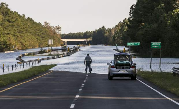 S.C. Highway 22 is flooded between SC-90 and SC-905 on Saturday, Sept. 22, 2018, in Conway, S.C. An officer with the South Carolina State Highway Patrol marks the water level to compare against previous days. The blocked road has traffic snarled around Conway and the Waccamaw River continues to rise past record levels. (Jason Lee/The Sun News via AP)