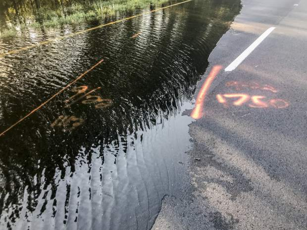 S.C. Highway 22 is flooded between SC-90 and SC-905 on Saturday, Sept. 22, 2018, in Conway, S.C. An officer with the S.C. State Highway Patrol marked the water level to compare against previous days. The blocked road has traffic snarled around Conway. (Jason Lee/The Sun News via AP)