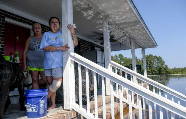 Candi Cisson, left, stands on the porch of the flooded home where she lives with her fiance Brian Terry on Bay Road Saturday, Sept. 22, 2018, in Brittons Neck, S.C. Most houses were cut off completely Saturday, with water on the front steps and creeping closer to the porch. Many residents were concerned that the flooding Great Pee Dee River will increase damage to their community. (Jason Lee/The Sun News via AP)