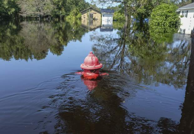 Flooding of the Little Pee Dee River is nearing the crest in Brittons Neck, S.C., but many residents are concerned that the floodwaters will increase damage to their community, Saturday, Sept. 22, 2018. (Jason Lee/The Sun News via AP)