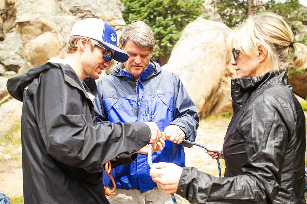 Aspen Alpine Guide Nate Rowland shows Debbie Stonecipher and KC Nau how to tie a prusik knot with rope on August 25 for a field planning and safety clinic up on Independence Pass.