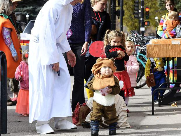 With their parents in tow, costumed children make their way around the block near Ninth Street and Cooper Avenue for the library's Halloween Parade after a special storytime on Tuesday.
