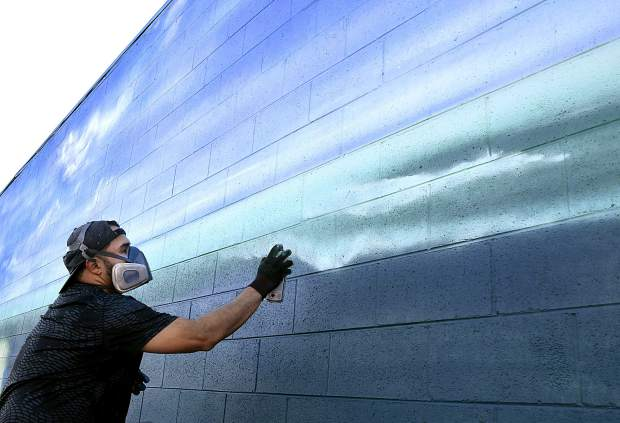 Artist Jeremy Velasquez of Rifle shapes the ocean waves, as he works on his latest mural on the east wall of Columbine Liquor at the intersection of Main Street and North Ninth Street in Silt. When finished, the mural will depict a beach scene inspired by the store owners' home state of California.