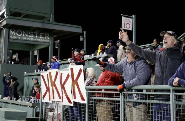 Boston Red Sox fans celebrate during the eighth inning in Game 2 of a baseball American League Championship Series against the Houston Astros on Sunday, Oct. 14, 2018, in Boston. (AP Photo/Elise Amendola)