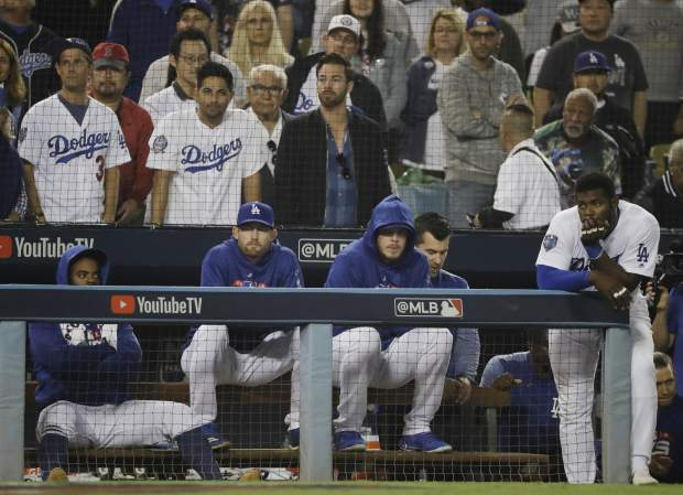 Los Angeles Dodgers' Yasiel Puig, right, and his teammates watches the eighth inning in Game 5 of the World Series baseball game against the Boston Red Sox on Sunday, Oct. 28, 2018, in Los Angeles. (AP Photo/David J. Phillip)