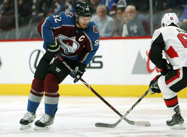 FILE--In this Friday, Oct. 26, 2018, file photograph, Colorado Avalanche left wing Gabriel Landeskog, left, works the puck past Ottawa Senators right wing Mark Stone in the first period of an NHL hockey game in Denver. The Colorado Avalanche trio of Landeskog, Nathan MacKinnon and Mikko Rantanen form the top line in hockey. The speedy group has a combined 55 points this season as Rantanen leads the league in points. The trio has helped lift Colorado to one of the best marks in the Western Conference this season. (AP Photo/David Zalubowski, File)