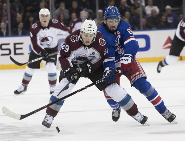 Colorado Avalanche center Nathan MacKinnon (29) and New York Rangers center Mika Zibanejad (93) chase a loose puck during the third period of an NHL hockey game, Tuesday, Oct. 16, 2018, at Madison Square Garden in New York. The Rangers won 3-2. (AP Photo/Mary Altaffer)