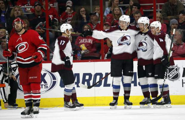 Colorado Avalanche's Gabriel Landeskog (92), of Sweden, celebrates his goal with Tyson Jost (17), Mikko Rantanen (96), of Finland and Tyson Barrie (4) during the second period of an NHL hockey game in Raleigh, N.C., Saturday, Oct. 20, 2018. The Carolina Hurricanes' Jordan Martinook (48) skates away. (AP Photo/Chris Seward)
