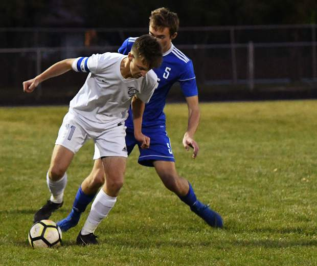 Roaring Fork Ram Aiden Sloan and Coal Ridge Titan Jack Price fight for possession of the ball during Thursday night's game at Roaring Fork High School.