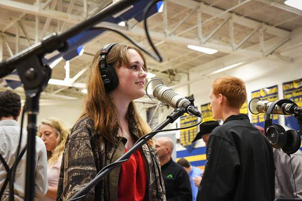 Grand Valley High School sophomore Kaydence Honer has fun talking into the radio mics at the KMTS table at the career fair held at Rifle High School on Wednesday moring.
