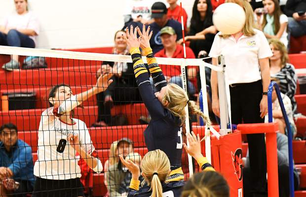 GLenwood Springs Demon Shanik Zambrano tips the ball over the net and past Rifle Bear Nikala Fitzsimmons during Tuesday night's game at Glenwood Springs High School.