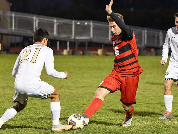 Glenwood Springs Demon Jackson Kruse attempts to get the ball past the defending Battle Mountain Huskey during Tuesday night's game at Stubler Memorial Field.