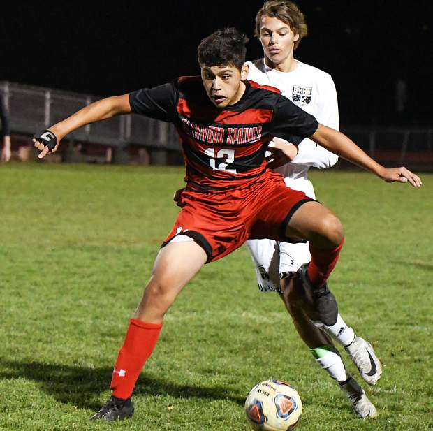 Glenwood Springs Demon Leo Mireles traps the ball down the during Tuesday night's game against the Battle Mountain Huskies at Stubler Memorial Field.
