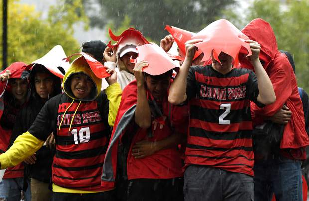 The Glenwood Springs High School boys soccer team takes cover under whatever they can find as an afternoon downpour drenches the parade route Friday.