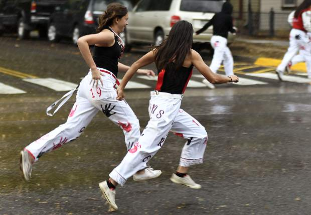 Glenwood High School students sprint down Pitkin Avenue on their way back to the school after a sudden downpour hit Glenwood Friday afternoon during the homecoming parade.