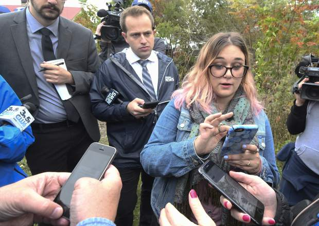 Karina Halse of Fort Ann, N.Y., right, talks to reporters and shares photos of her sister Amanda Halse who died in Saturday's fatal limousine crash in Schoharie, N.Y., Monday, Oct. 8, 2018. A limousine loaded with revelers heading to a 30th birthday slammed into an SUV parked outside a store, killing all people in the limo and two pedestrians. (AP Photo/Hans Pennink)