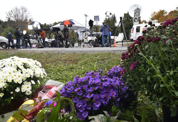 Television networks broadcast at the roadside memorial scene of Saturday's fatal limousine crash in Schoharie, N.Y., Monday, Oct. 8, 2018. A limousine loaded with people headed to a birthday party blew a stop sign at the end of a highway and slammed into an SUV parked outside a store, killing all people in the limo and a few pedestrians, officials and relatives of the victims said. (AP Photo/Hans Pennink)