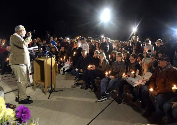 Rev. Kent McHeard speaks to family members and friends during a candlelight vigil memorial at Mohawk Valley Gateway Overlook Pedestrian Bridge in Amsterdam, N.Y., Monday, Oct. 8, 2018. The memorial honored 20 people who died in Saturday's fatal limousine crash in Schoharie, N.Y., (AP Photo/Hans Pennink)