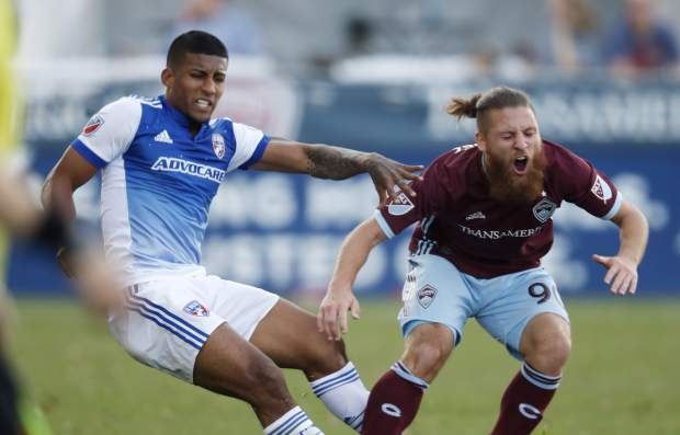 Colorado Rapids midfielder Enzo Martinez, right, reacts after getting tangled up with FC Dallas midfielder Santiago Mosquera while pursuing the ball in the second half of an MLS soccer match Sunday, Oct. 28, 2018, in Commerce City, Colo. The Rapids won 2-1. (AP Photo/David Zalubowski)