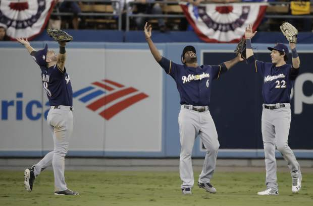 Milwaukee Brewers' Ryan Braun, Lorenzo Cain and Christian Yelich celebrate after Game 3 of the National League Championship Series baseball game against the Los Angeles Dodgers Monday, Oct. 15, 2018, in Los Angeles. The Brewers won 4-0 to take a 2-1 lead in the series. (AP Photo/Jae Hong)
