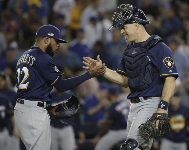 Milwaukee Brewers' Jeremy Jeffress and catcher Erik Kratz celebrate after Game 3 of the National League Championship Series baseball game against the Los Angeles Dodgers Monday, Oct. 15, 2018, in Los Angeles. The Brewers won 4-0 to take a 2-1 lead in the series. (AP Photo/Jae Hong)