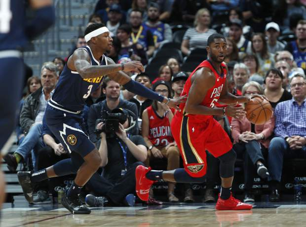 New Orleans Pelicans guard E'Twaun Moore, right, picks up a loose ball as Denver Nuggets forward Torrey Craig defends in the first half of an NBA basketball game Monday, Oct. 29, 2018, in Denver. (AP Photo/David Zalubowski)