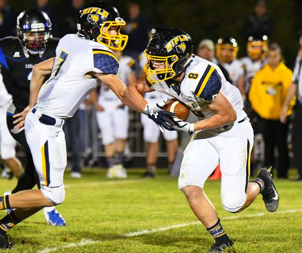 Rifle Bear Holden Stutsman hands the ball off to Levi Warfel during Friday night's game against the Coal Ridge Titans.