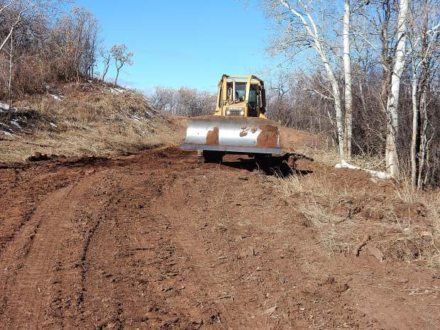 A front loader is among the heavy equipment working on Basalt Mountain Road and Cattle Creek Road. Operators are building check dams and water diversions to guard against spring runoff.