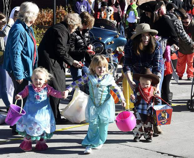 Trick-or-treaters dash from one stop to the next during the Garfield County Library Rifle Branch's Halloween Parade Wednesday in Rifle. Over 450 people attended this year's event.