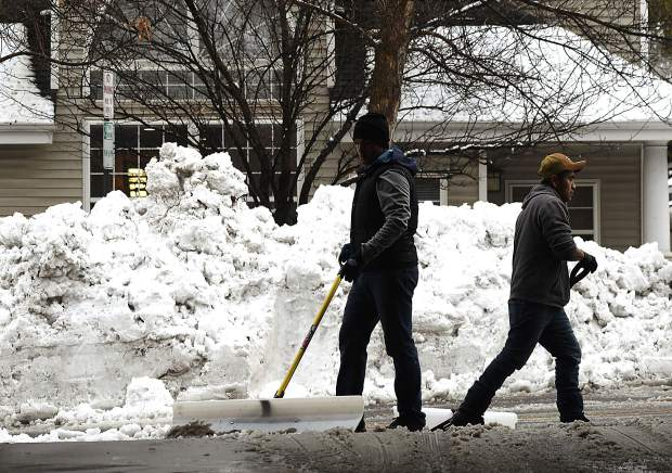 Mario Bargas and Victor Gusman clear the snow from the sidewalks around the parking garage in downtown Glenwood Springs Thursday. Heavy snowfall hit the Roaring Fork Valley Wednesday evening. Friday's forecast is calling for more snow and cooler temperatures on the Western Slope.