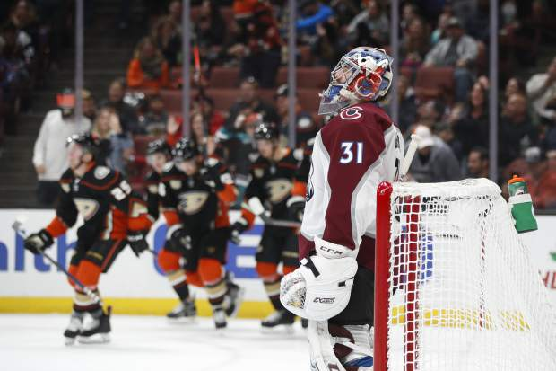 Colorado Avalanche goaltender Philipp Grubauer, of Germany, stands in front of his net as the Anaheim Ducks players celebrate a goal by Ondrej Kase during the second period of an NHL hockey game Sunday, Nov. 18, 2018, in Anaheim, Calif. (AP Photo/Jae C. Hong)