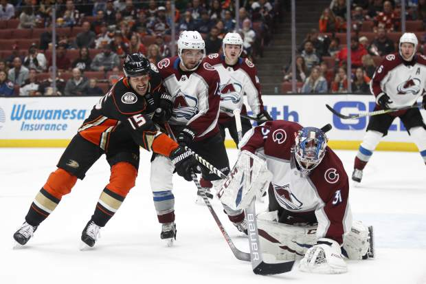 Colorado Avalanche goaltender Philipp Grubauer, right, of Germany, stops a shot as Anaheim Ducks' Ryan Getzlaf, left, is held back by Avalanche's Alexander Kerfoot during the second period of an NHL hockey game Sunday, Nov. 18, 2018, in Anaheim, Calif. (AP Photo/Jae C. Hong)