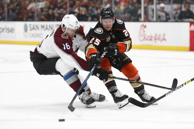 Anaheim Ducks' Ondrej Kase, right, of the Czech Republic, reaches for the puck next to Colorado Avalanche's Nikita Zadorov, of Russia, during the second period of an NHL hockey game Sunday, Nov. 18, 2018, in Anaheim, Calif. (AP Photo/Jae C. Hong)