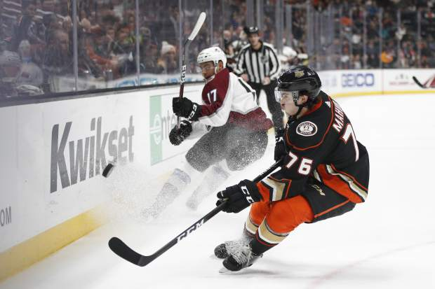 Anaheim Ducks' Josh Mahura, front, and Colorado Avalanche's Tyson Jost fight for the puck during the first period of an NHL hockey game Sunday, Nov. 18, 2018, in Anaheim, Calif. (AP Photo/Jae C. Hong)
