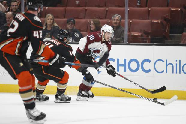 Colorado Avalanche's Sven Andrighetto, center, of Switzerland, moves the puck under pressure by Anaheim Ducks' Adam Henrique during the first period of an NHL hockey game Sunday, Nov. 18, 2018, in Anaheim, Calif. (AP Photo/Jae C. Hong)