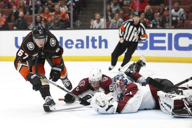 Anaheim Ducks' Rickard Rakell, left, of Sweden, loses his stick as he tries to score against Colorado Avalanche goaltender Philipp Grubauer, of Germany, under defense by Erik Johnson during the second period of an NHL hockey game Sunday, Nov. 18, 2018, in Anaheim, Calif. (AP Photo/Jae C. Hong)