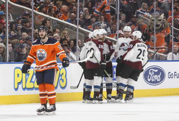 Colorado Avalanche players celebrate a goal as Edmonton Oilers' Tobias Rieder (22) skates past during second period NHL hockey action in Edmonton, Alberta on Sunday Nov. 11, 2018. (Jason Franson/The Canadian Press via AP)