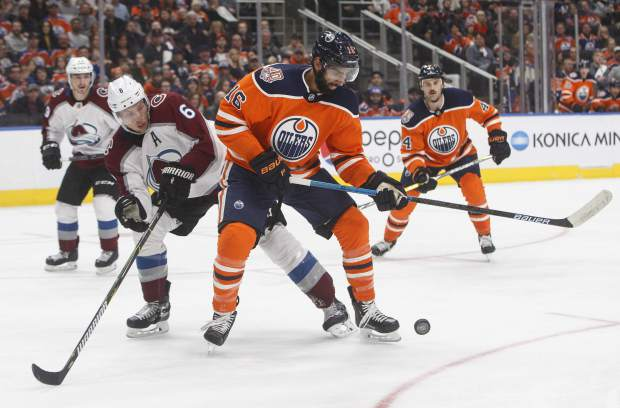 Colorado Avalanche' Erik Johnson (6) and Edmonton Oilers' Jujhar Khaira (16) battle for the puck during second period NHL hockey action in Edmonton, Alberta on Sunday Nov. 11, 2018. (Jason Franson/The Canadian Press via AP)