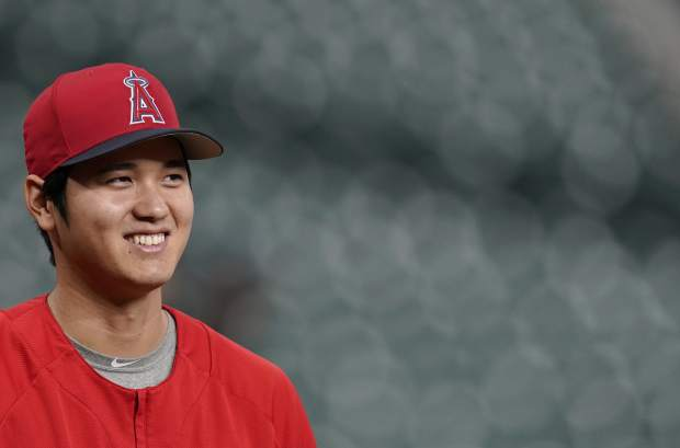 In this Sept. 21, 2018 photo Los Angeles Angels' Shohei Ohtani, of Japan, waits to stretch during batting practice before a baseball game against the Houston Astros in Houston. Ohtani has been voted American League Rookie of the Year after becoming the first player since Babe Ruth with 10 homers and four pitching wins in the same season. Ohtani, a 24-year-old right-hander who joined the Angels last winter after five seasons with Japan's Nippon Ham Fighters, received 25 first-place votes and four seconds for 137 points from the Baseball Writers' Association of America in balloting announced Monday, Nov. 12, 2018. (AP Photo/David J. Phillip)